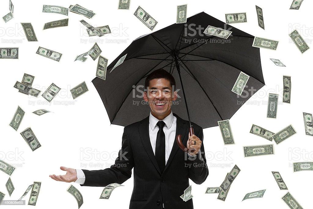 Raining money on a businessman stock photo