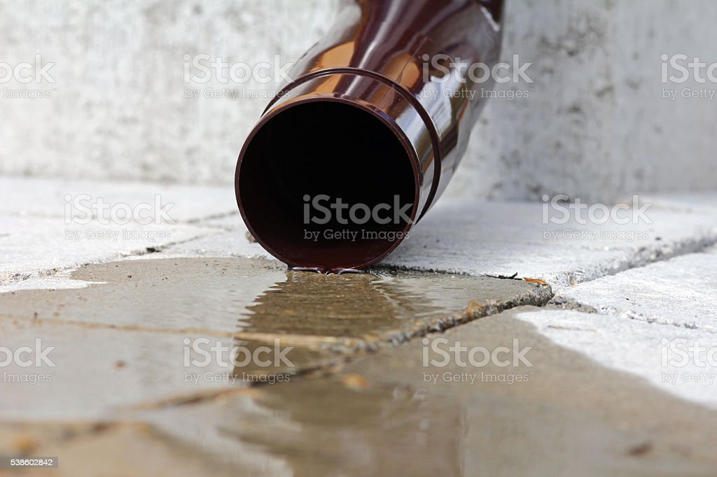 Rainwater flowing from a downspout on a house stock photo
