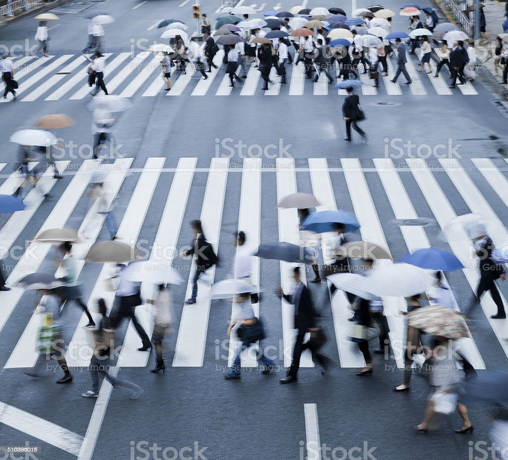 busy crosswalk scene on a rainy day with blur motion