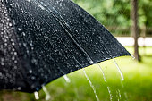 Rainy day. Raindrops falling on black umbrella outdoors. Spring, summer.