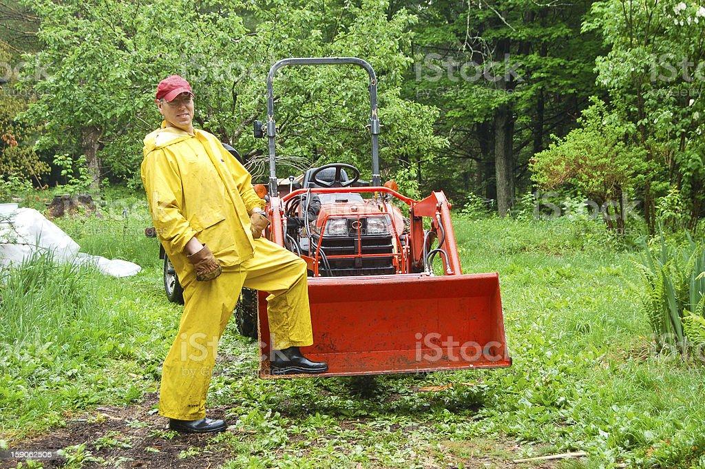 Rainy day tractor man stock photo