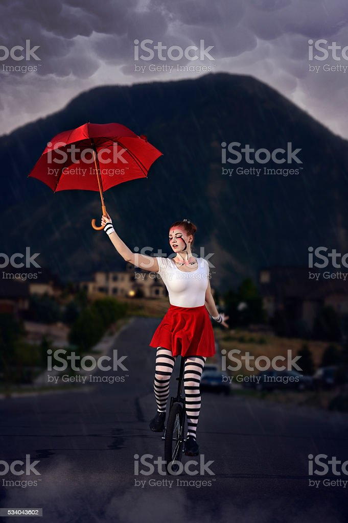 Rainy Night Acrobat With Red Umbrella stock photo