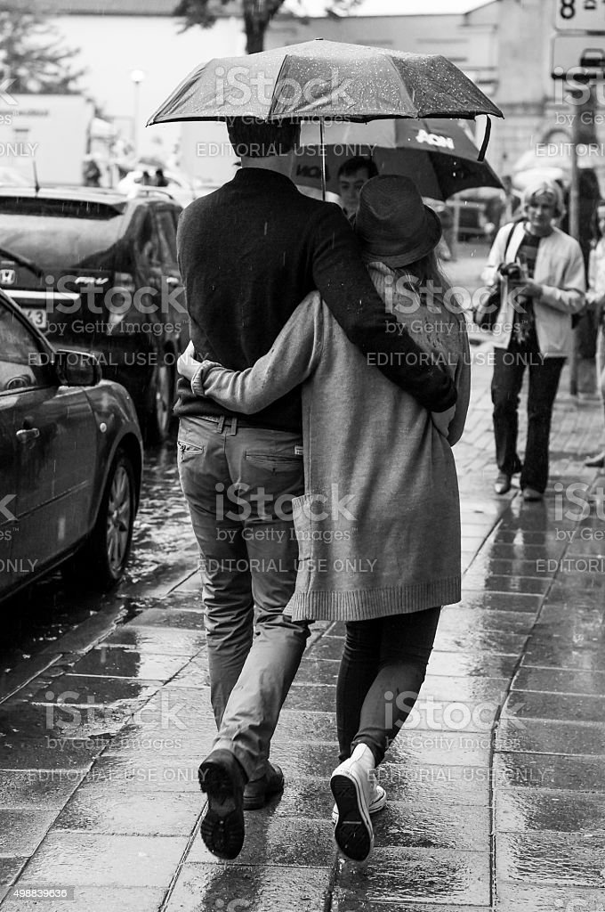 Rainy streets synchronously walking couple. Black and White. stock photo