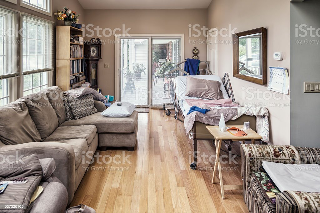 Raised Hospital Bed In Cluttered Private Residence Living Room stock photo
