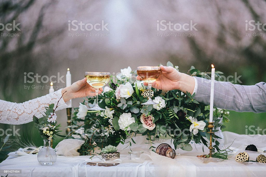 Raising glasses with champagne at the wedding table stock photo