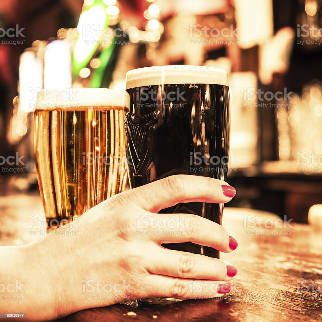 Raising up a pint of stout beer in a pub stock photo
