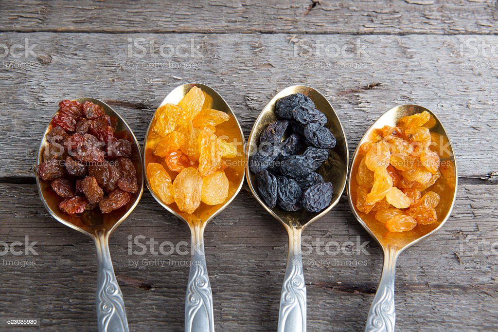 Raisins in metal spoons on wooden table stock photo