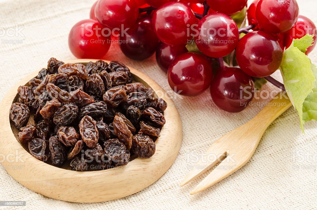 Raisins on a wooden dish and fresh red grapes. stock photo