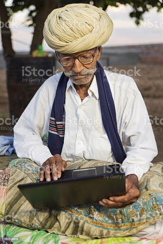Rajasthani old man using laptop. India royalty-free stock photo