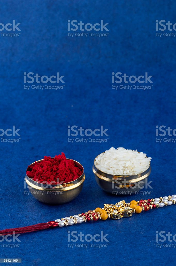 Rakhi or Rakshabandhan Greeting. Rakhi with rice grains and kumkum stock photo