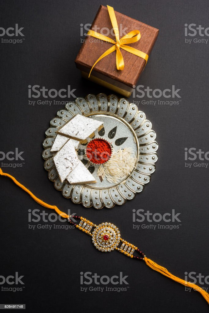 Raksha Bandhan - Rakhi and gift with sweet kaju katli or mithai and rice grains and kumkum in a decorative plate. Traditional Indian wrist band which is a symbol of love between Brothers and Sisters. stock photo