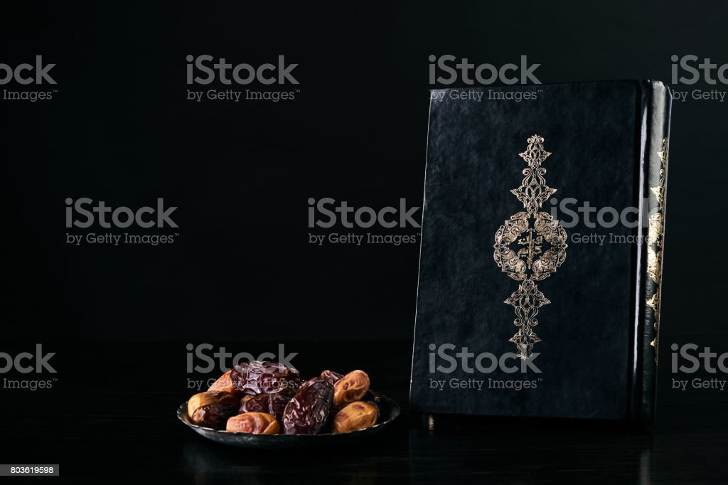 Ramadan atmosphere, Quran/ Koran Kareem book and silver dish with dry dates isolated on black background with copy space stock photo
