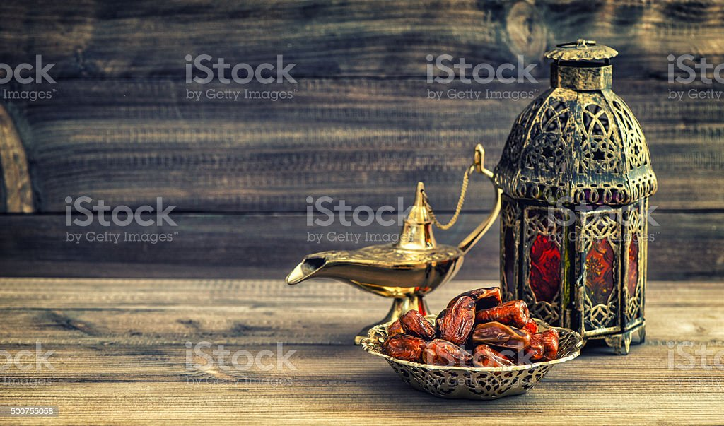 Ramadan lamp and dates on wooden background. Oriental lantern stock photo