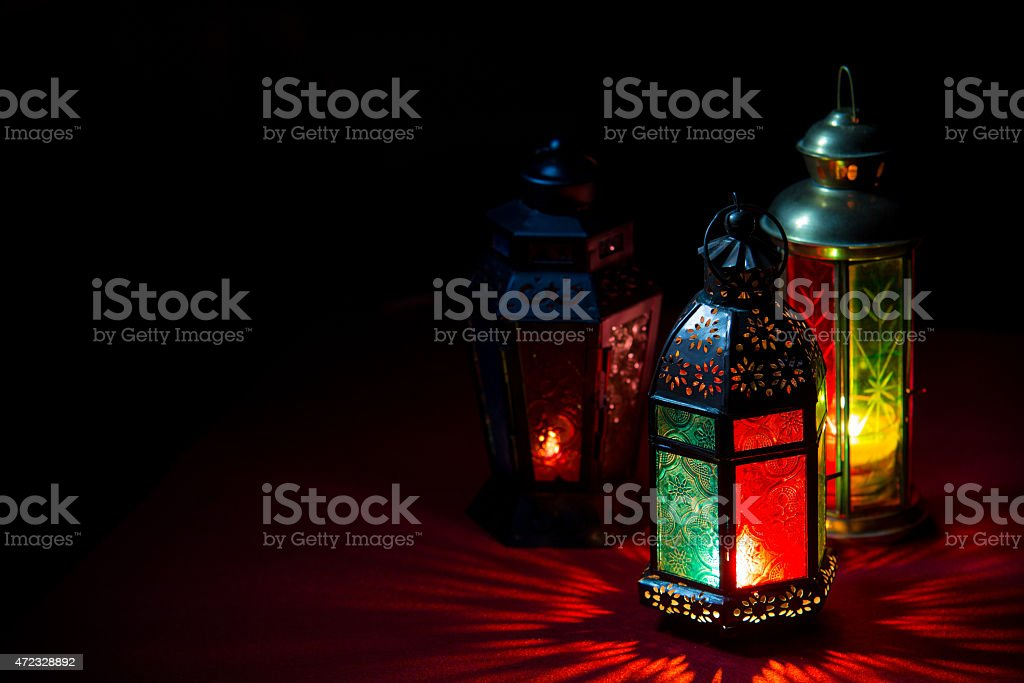 3 Ramadan lanterns illuminated with color glass on black stock photo