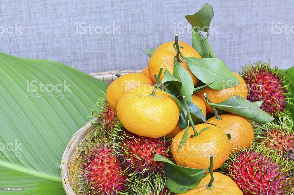Rambutan and orange  in the basket placing on green leaf royalty-free stock photo