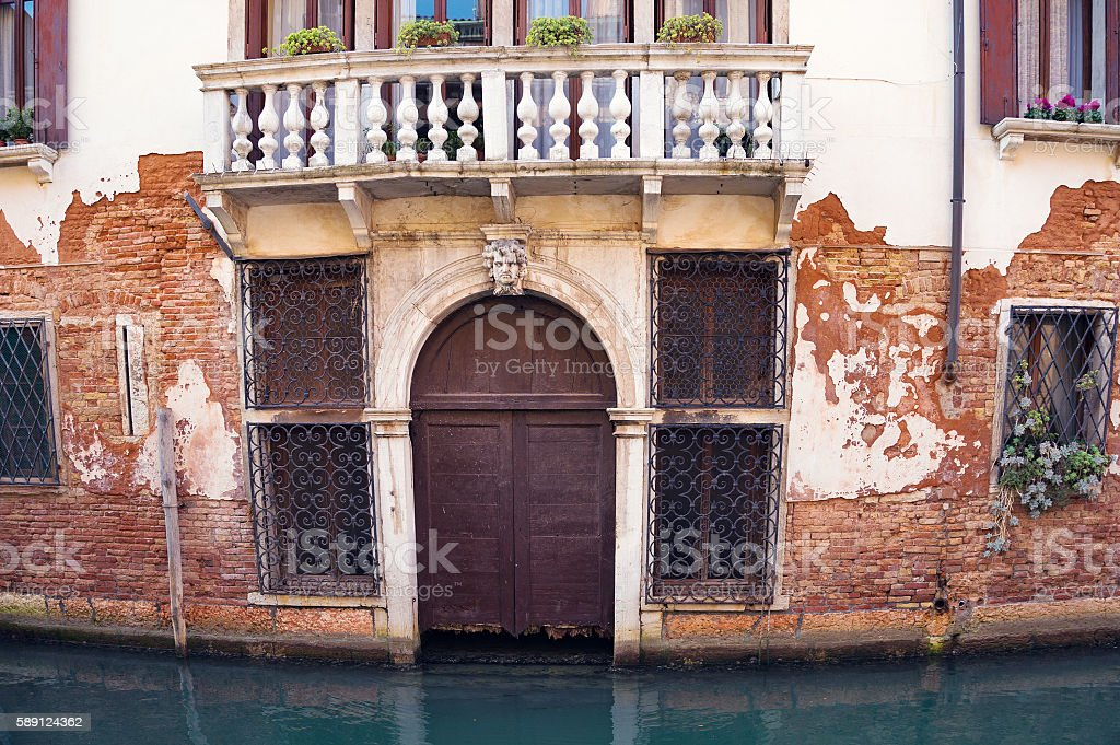 Ramshackle door of typical Venice residential house. Italy stock photo