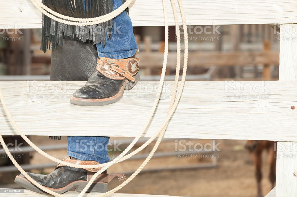Ranch: Cowboy climbing fence to corral. stock photo