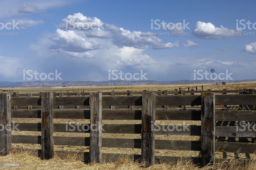 Ranch Fence, Old Windmill and Cloudy Sky in Background royalty-free stock photo