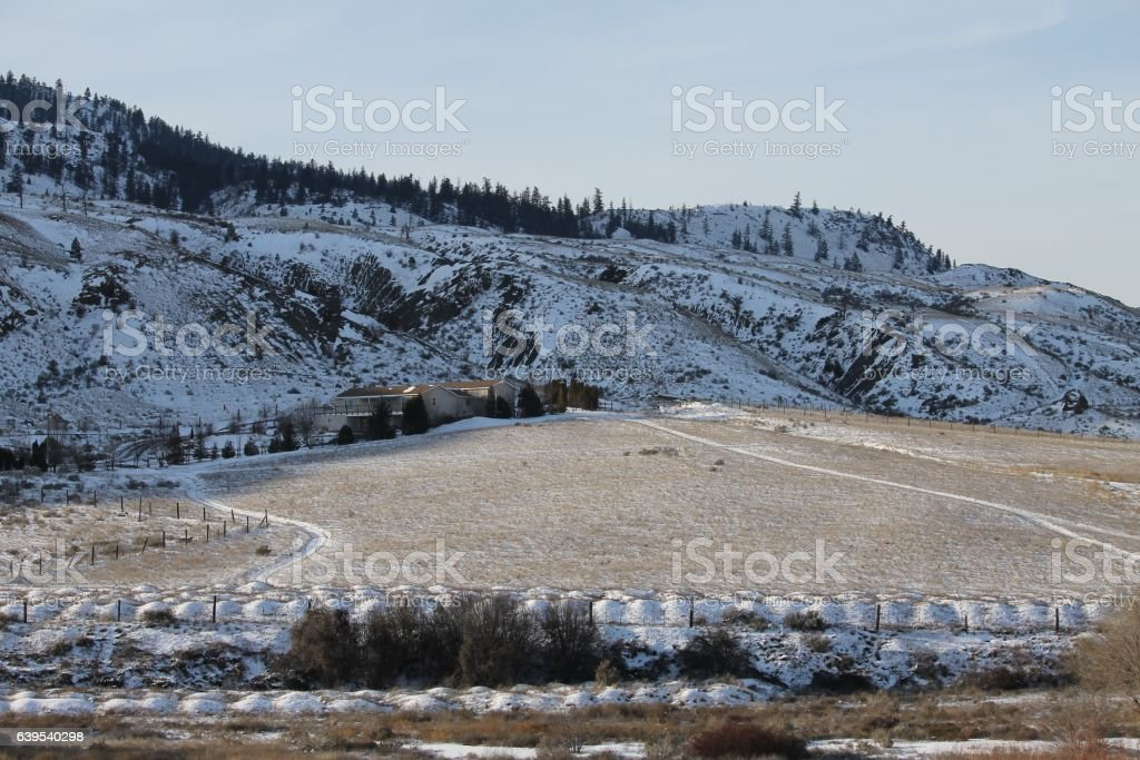 Ranch home in the wintery hills stock photo