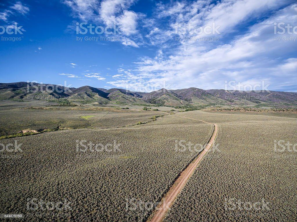 ranch road and Medicine Bow Mountains stock photo
