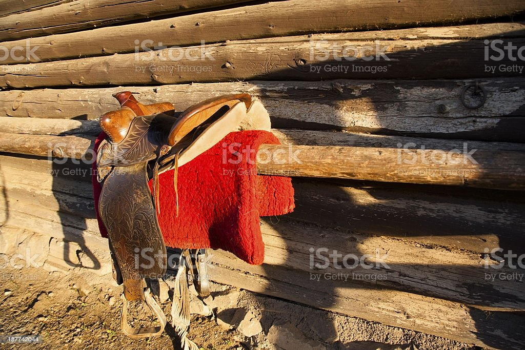Ranch:  Western saddle and blanket beside log tack room stock photo