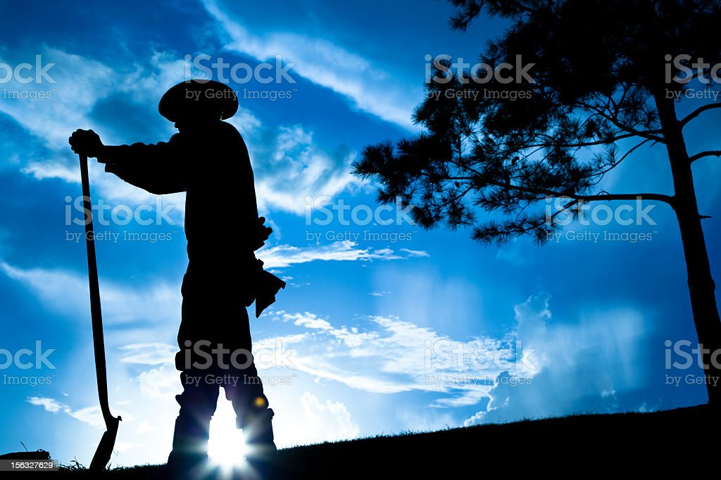Rancher farmer overlooking field after rain storm. Sunset. Silhouette. Sky. royalty-free stock photo