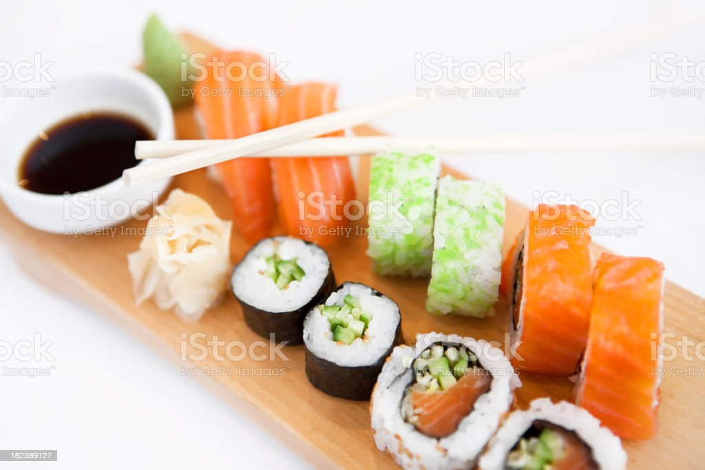 A range of sushi on a wooden board with soy sauce royalty-free stock photo