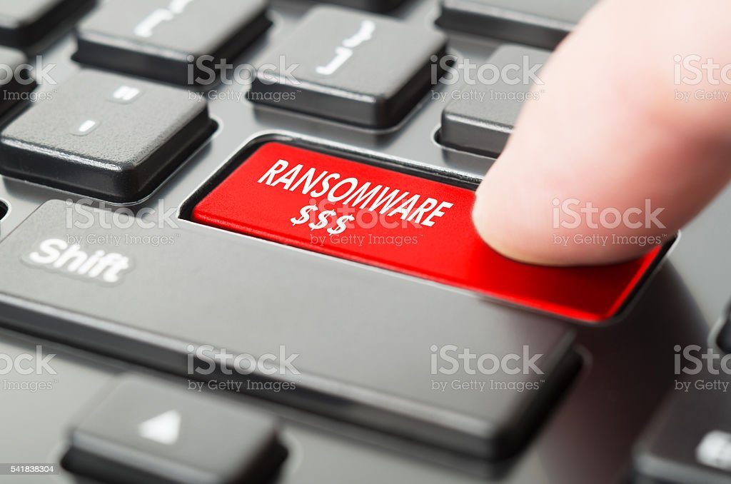 Ransomware written on keyboard button with finger pressing on it stock photo