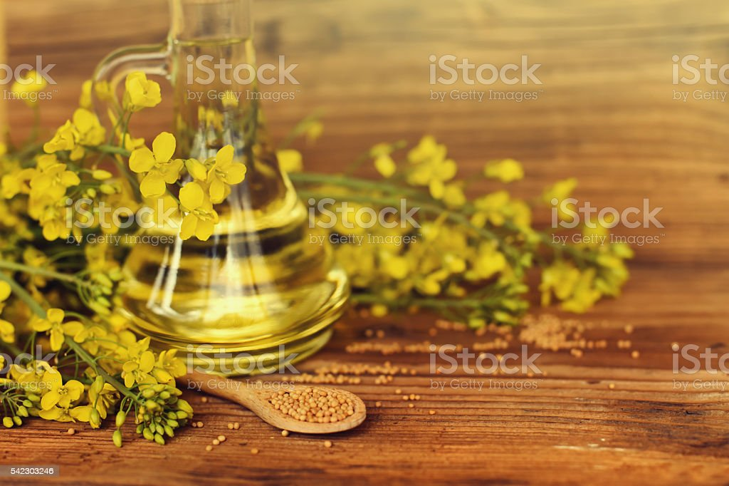 Rapeseed oil with rape flowers. stock photo