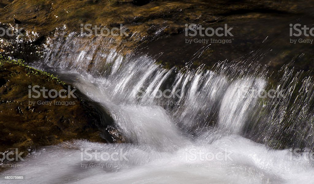Rapido flusso scorre tra pietre foto stock royalty-free