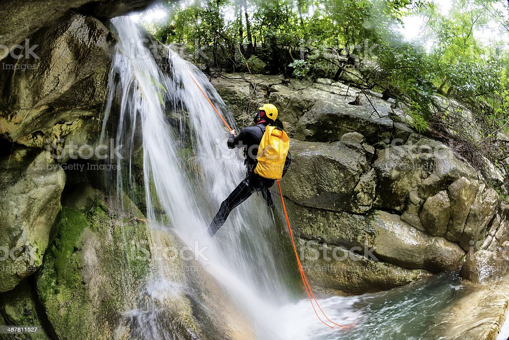 Rappeling down the waterfall stock photo