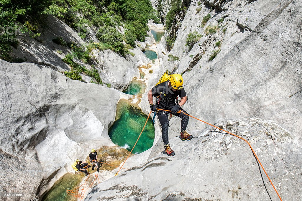 Rappeling in the canyon with water pools stock photo