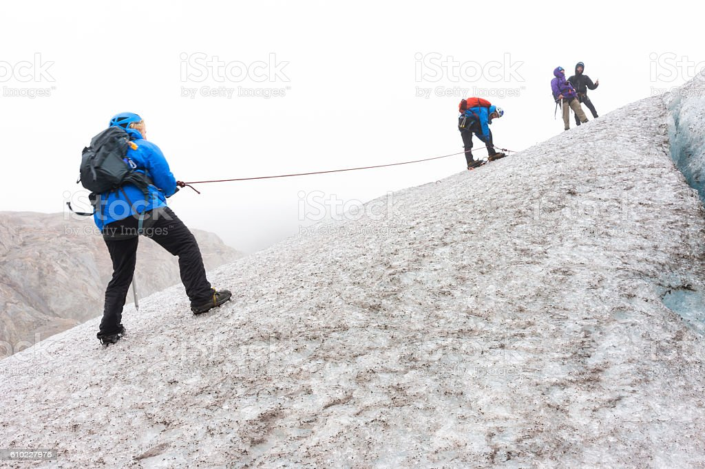 Rappelling down icy slope on Lemon Glacier stock photo