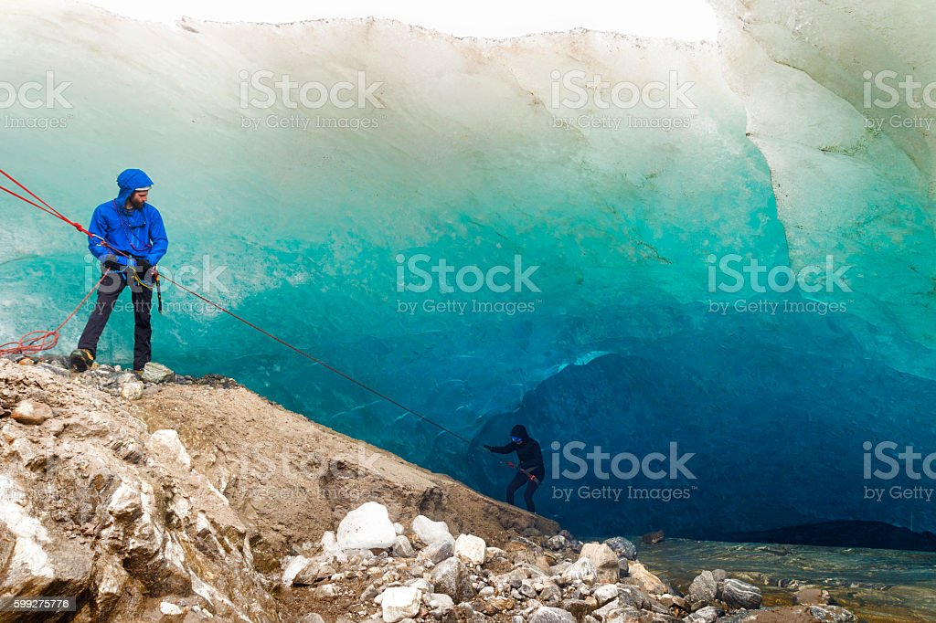 Rappelling into a glacial ice cave stock photo