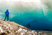 Rappelling into a glacial ice cave