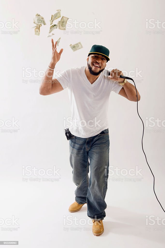 Rapper sings into microphone while throwing cash in the air royalty-free stock photo