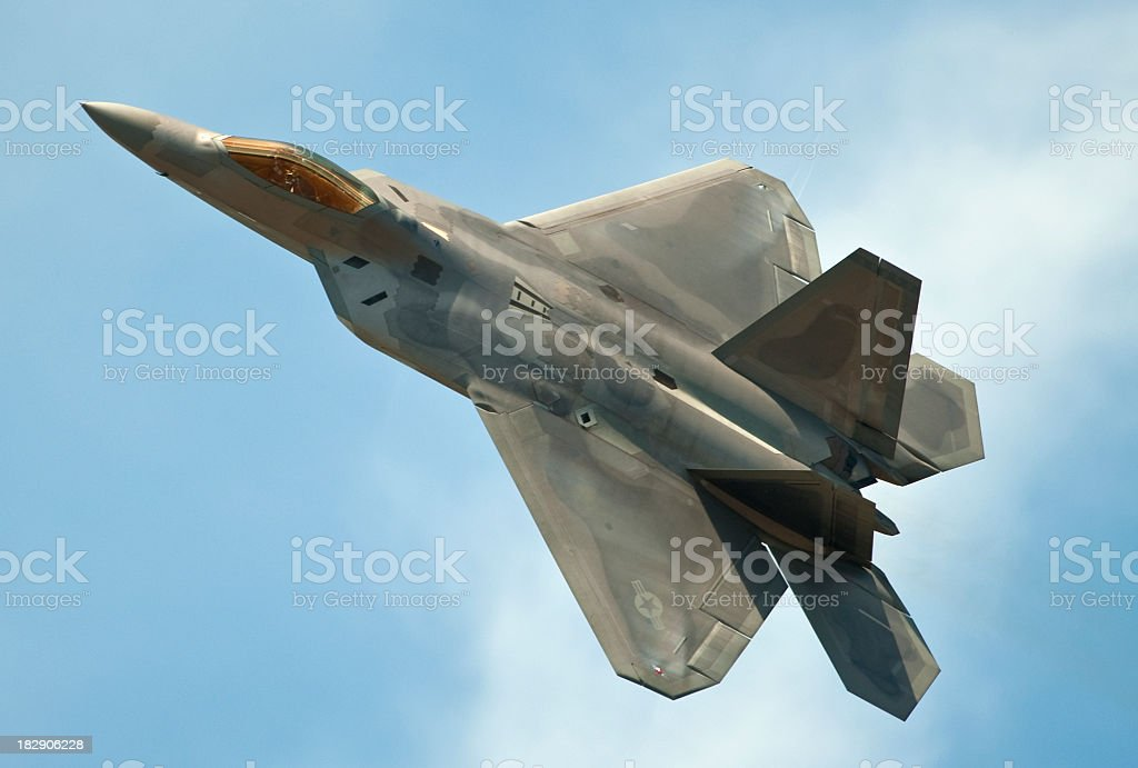 F22 Raptor jet flying in clear blue sky stock photo