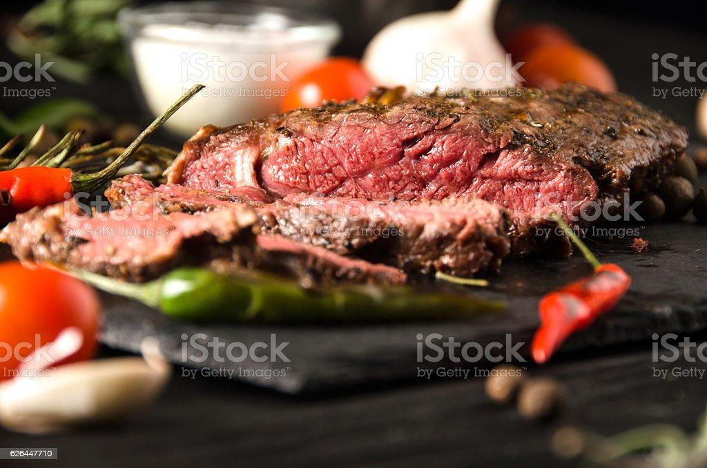 rare steak black square plate spices rosemary stock photo