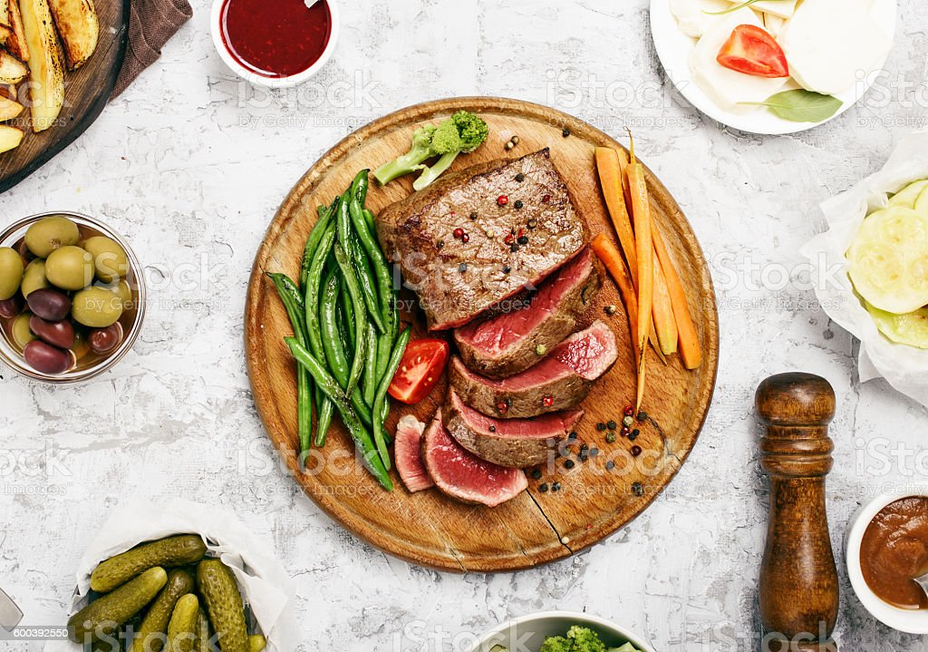 Rare steak with vegetable garnish and sauces stock photo