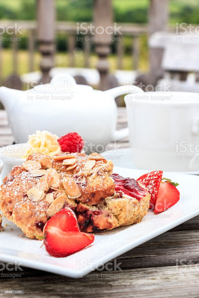 Rasberry and almond scone strawberries with hot tea stock photo