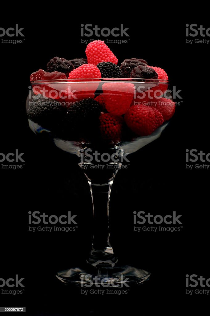 raspberries and blackberries, glass closeup isolated, candle, candy stock photo