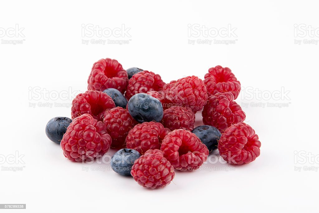 Raspberries and blueberries on a white background stock photo