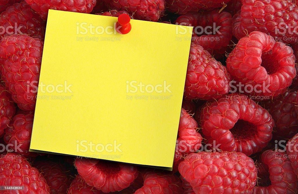 raspberries and yellow note stock photo