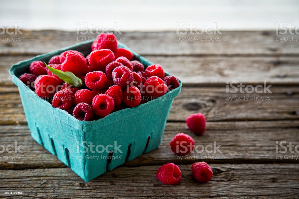 Raspberries in blue-green basket stock photo