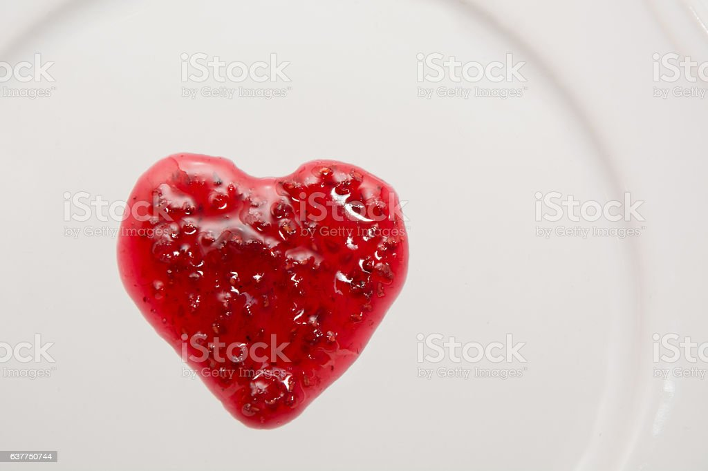 Raspberries jam in shape of heart isolated on white background. stock photo