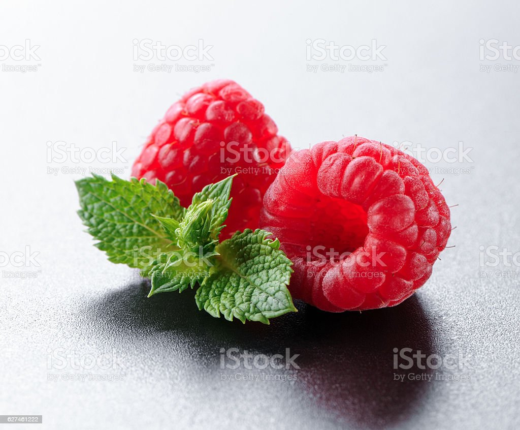 raspberries with mint leaves  on black background stock photo