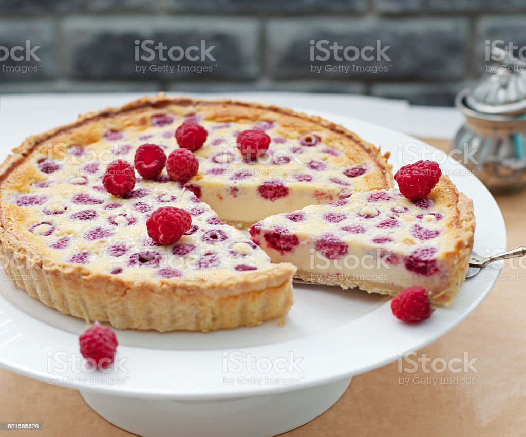 Raspberry, blueberry and white chocolate tart on white plate stock photo