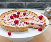 Raspberry, blueberry and white chocolate tart on white plate