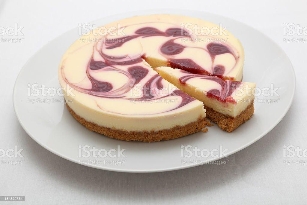 raspberry cheesecake on round plate plain background stock photo
