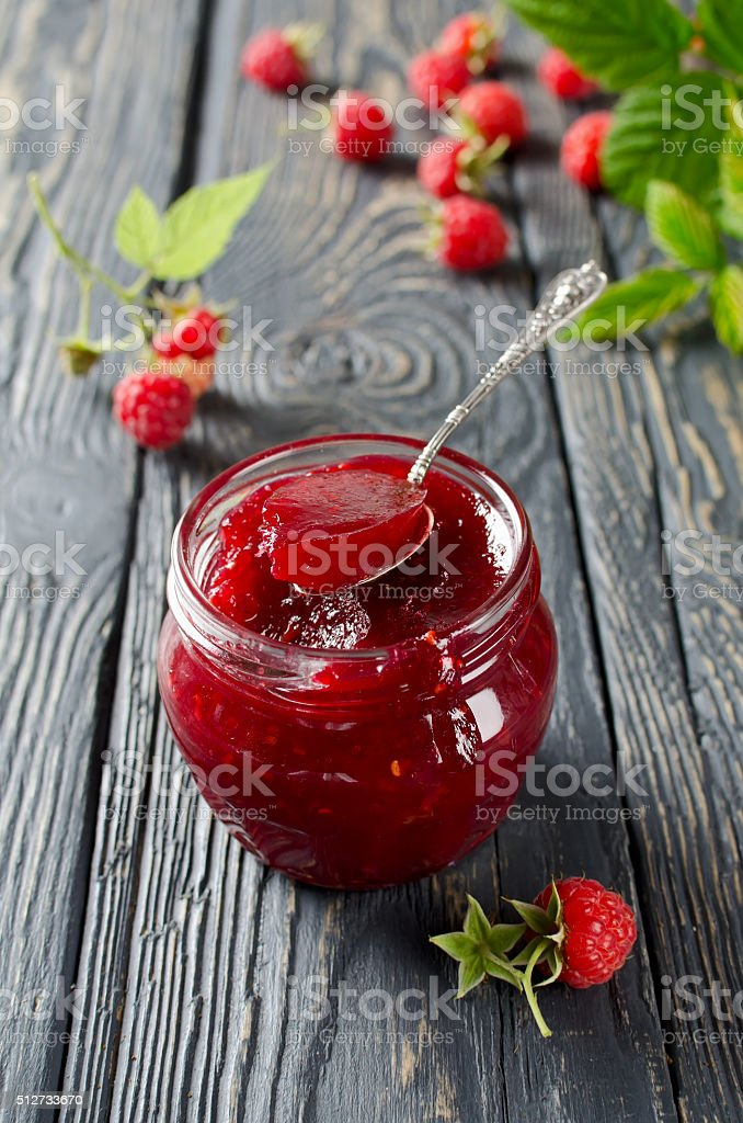 Raspberry jam on a rustic wooden table stock photo